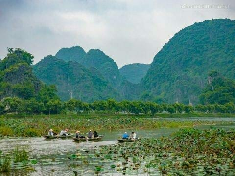 Tour boats making their way down the scenic river at Tam Coc, in Ninh Binh, Vietnam, on September 2015
