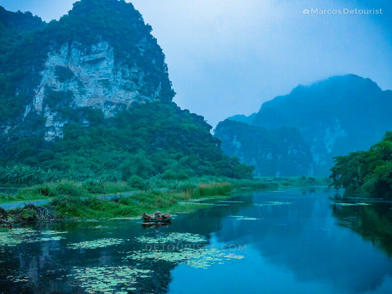 Local on a boat filled with gathered firewood, at dusk, at Trang An riverside, Ninh Binh, Vietnam, on September 2015